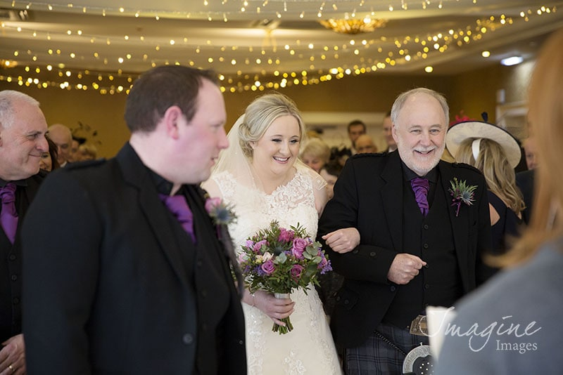 Bride walks down the aisle to meet groom on wedding day at Gleddoch House Hotel